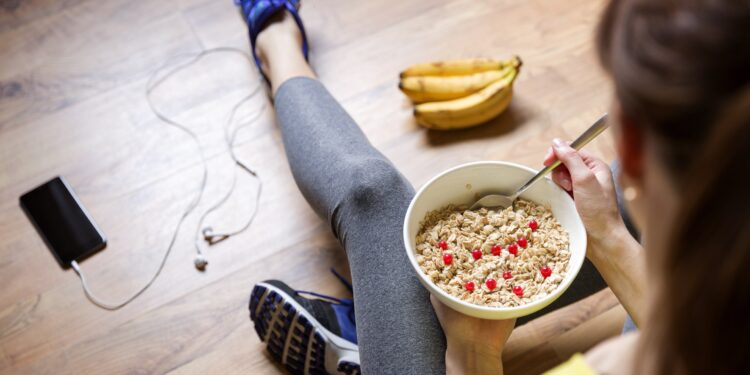 Eine Frau in Sportkleidung isst Müsli.
