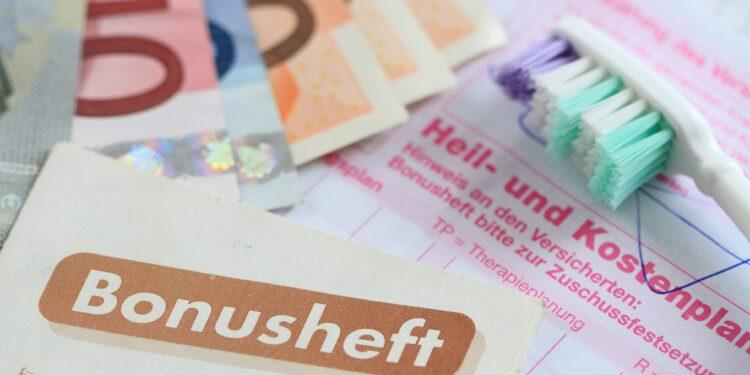 Heil- und Kostenplan mit einem Bonusheft, einer Zahnbürste und mehrere Euroscheine