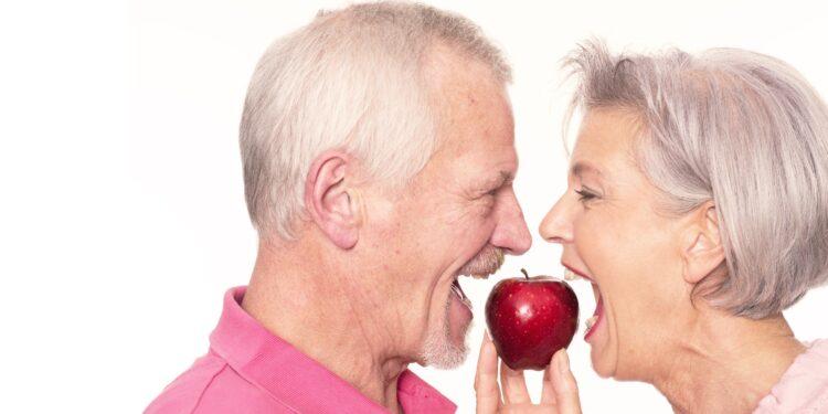 Ein älteres Pärchen beißt von zwei Seiten in einen Apfel.