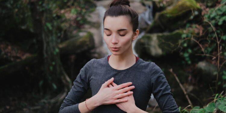 Eine Frau führt eine Atemübung in der Natur durch.