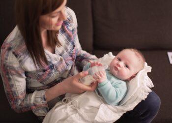 Eine Frau füttert ein Baby mit einer Flasche.