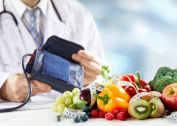 Obst und Gemüse und ein Maßband auf einem Tisch vor einem Arzt mit einem Blutdruckmessgerät