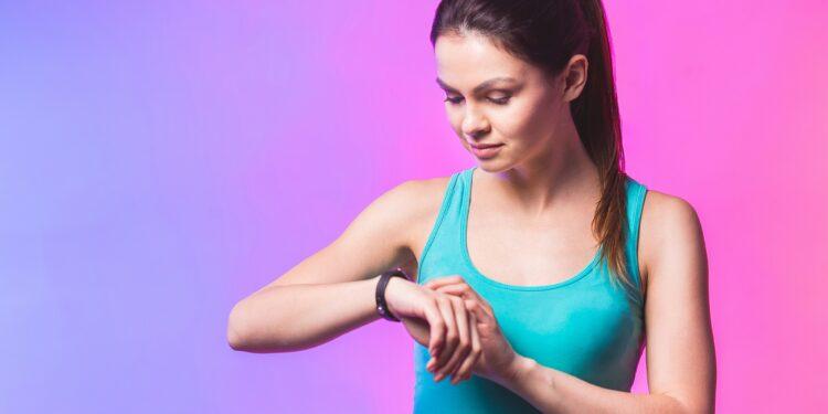 Frau schaut auf ihren Fitness-Tracker