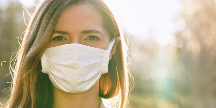 Junge Frau trägt eine Mund-Nasen-Bedeckung