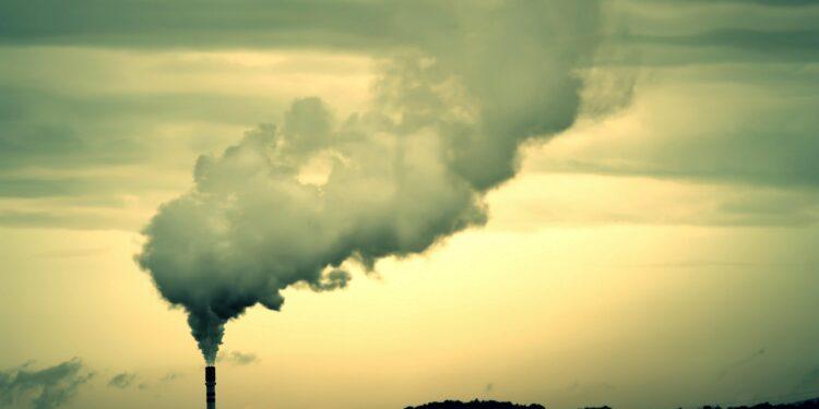 Ein in weiter Ferne zu sehender Fabrik-Schornstein mit großer Rauchwolke