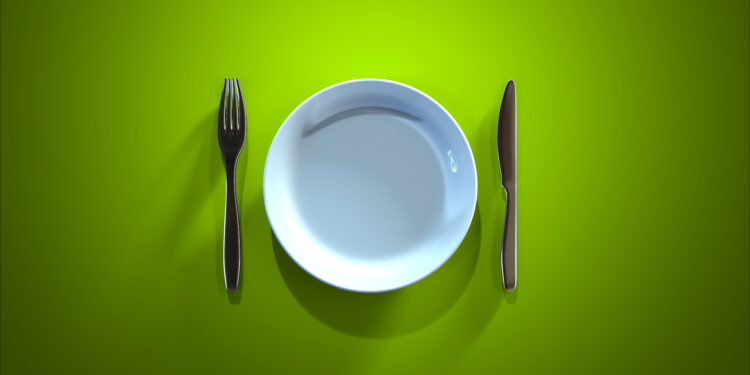 Ein leerer Teller, ein Messer und eine Gabel auf einer grünen Oberfläche
