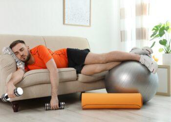 Mann mit Trainingsgeräten schläft auf dem Sofa.