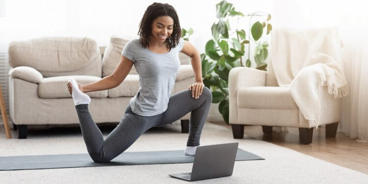 Frau trainiert im Wohnzimmer vor dem Laptop auf Yogamatte