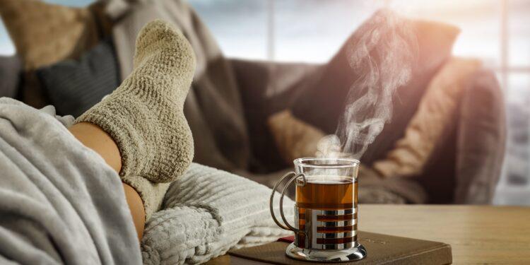 Eine Tasse heißer Tee neben Füße in dicken Socken auf einem Tisch