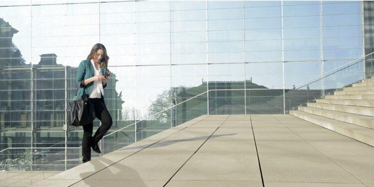 Frau mit Smartphone beim Treppensteigen