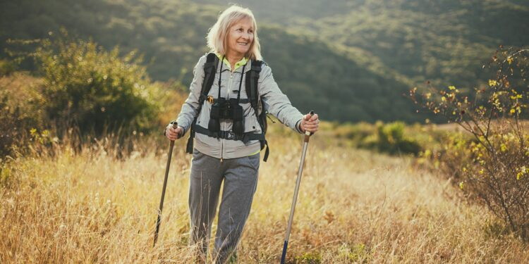 Seniorin mit Fernglas beim Wandern