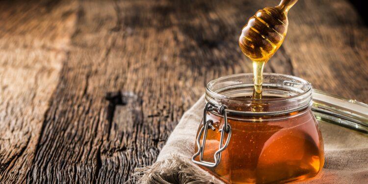 Honigglas mit Schöpflöffel auf einem altem Holztisch