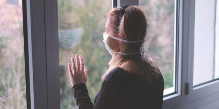 Frau schaut aus dem Fenster.