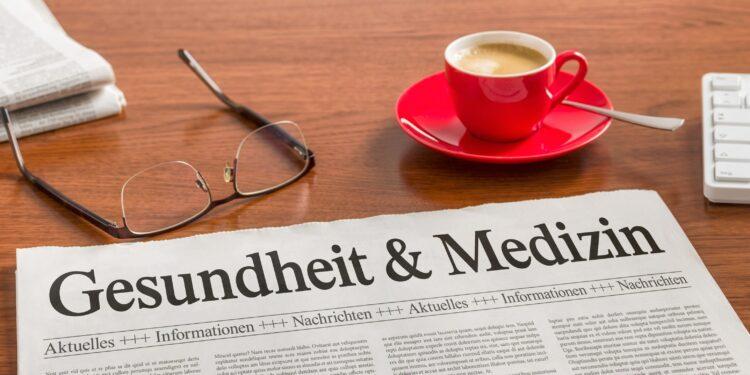Auf einem Schreibtisch befinden sich eine Brille, eine Zeitung und eine Tasse Kaffee.