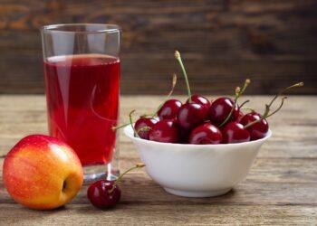 Ein Apfel, eine Schale mit Kirschen und ein Glas mit Saft stehen auf einer hölzernen Oberfläche.