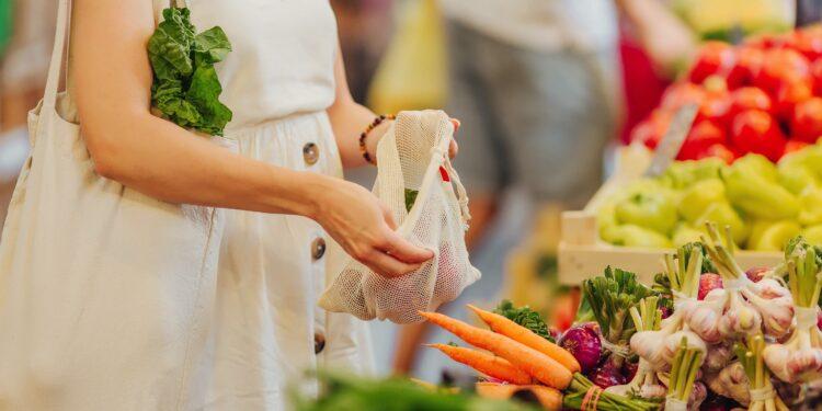Eine Frau packt auf einem Markt Obst und Gemüse in einen Beutel