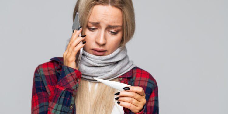 Junge Frau mit Erkältung blickt auf ein Fieberthermometer während sie mit einem Smartphone telefoniert