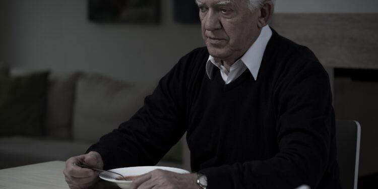 Älterer Mann ohne Appetit sitzt vor seinem Teller