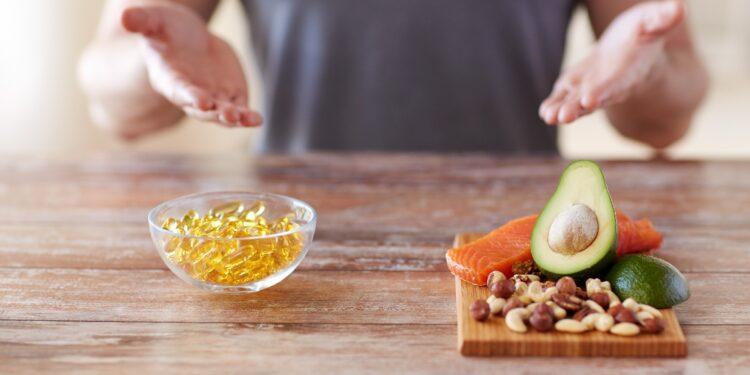 Auf einem Tisch steht ein Teller mit gesunden Lebensmitteln und eine Schale voll Vitaminpräparaten.