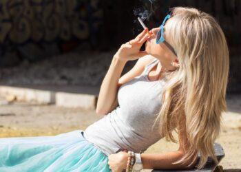 Junge Frau liegt rauchend in der Sonne.