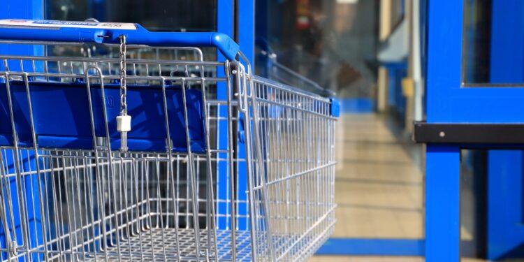 Blauer Einkaufswagen vor Ladentür