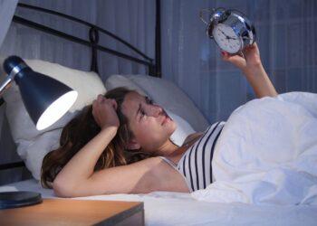 Frau betrachtet spät in der Nach ihren Wecker.