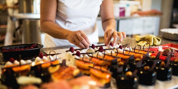 Eine Frau dekoriert Süßspeisen.