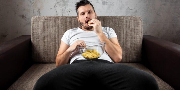 Mann vor dem Fernseher auf Sofa mit Chips.