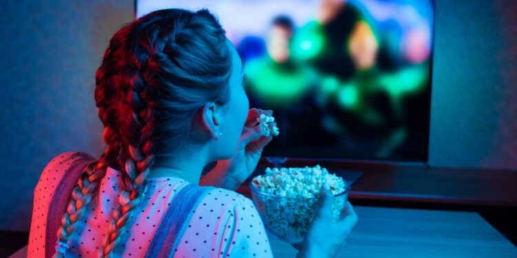 Mädchen sitzt vor dem Fernseher und isst Popcorn