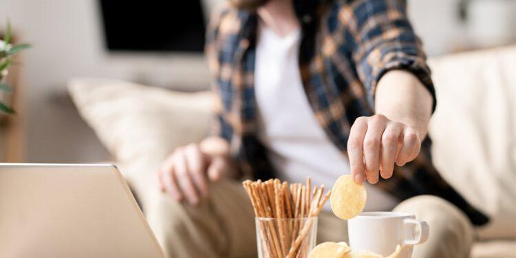 Mann sitzt am Laptop und greift zu Chips
