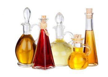 Verschiedene Speiseöle in unterschiedlichen Farben und Flachen vor einem weißen Hintergrund.