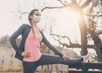 Junge Frau mit Mund-Nasen-Bedeckung macht auf einer Bank im Freien Dehnübungen