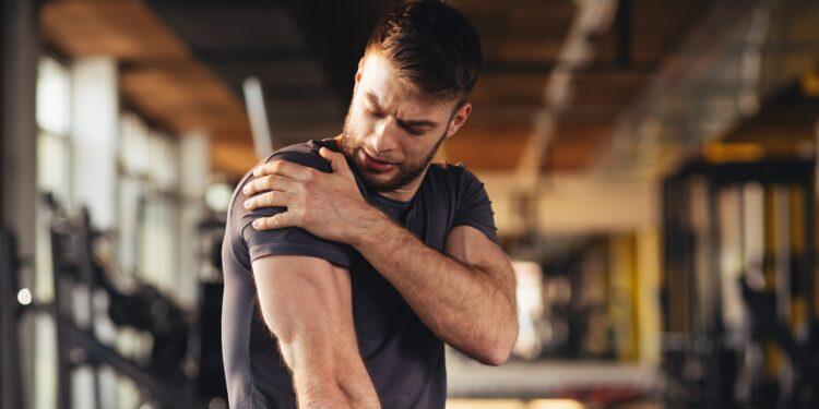Ein Mann fasst sich in einem Fitnessstudio an die Schulter.