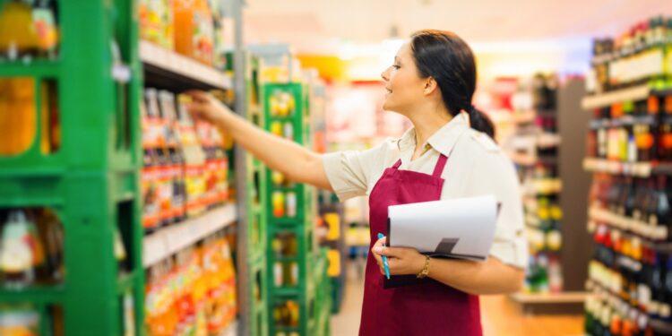 Eine Angestellte im Supermarkt kontrolliert die Getränke.