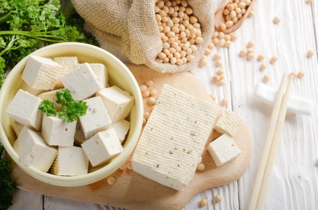 Tofu auf einem Holzbrett und in einer Schüssel neben einem Sack mit Sojabohnen