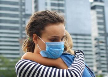 Mutter mit Mundschutz umarmt ihr Kind