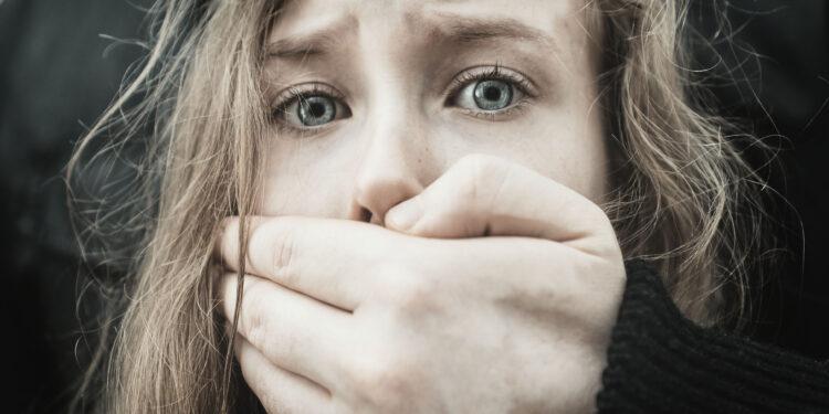 Verängstigtem Mädchen wird der Mund zugehalten.