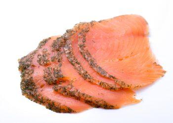 Einige Scheiben graved Lachs vor einem weißen Hintergrund.
