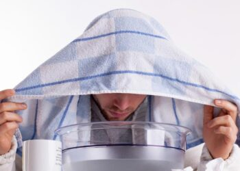 Ein Mann mit einem Handtuch über dem Kopf beugt sich über eine mit Flüssigkeit gefüllte Schüssel.