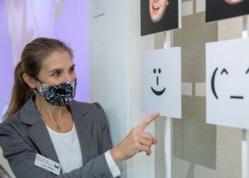 Eine Frau mit Mund-Nasenschutz steht vor einer Tafel.