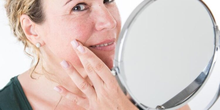 Eine Frau mit gerötetem Gesicht schaut in einen Spiegel.
