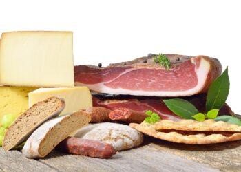 Verschiedene Käsesorten, Schinken und Brot liegen auf einem Holztisch.