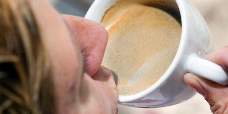 Eine Person nimmt einen Schluck Kaffee aus einer Tasse.