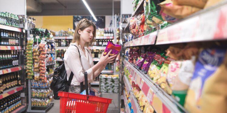 Eine junge Frau nimmt eine Packung Chips aus einem Regal im Supermarkt.