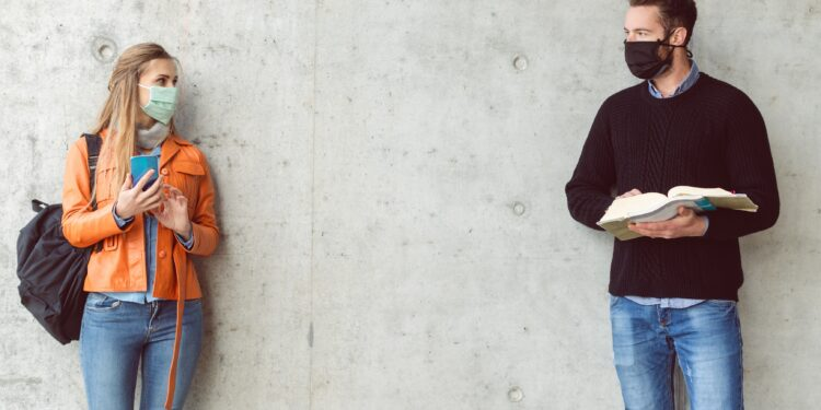Eine Frau und ein Mann mit Gesichtsmasken stehen mit Abstand zueinander