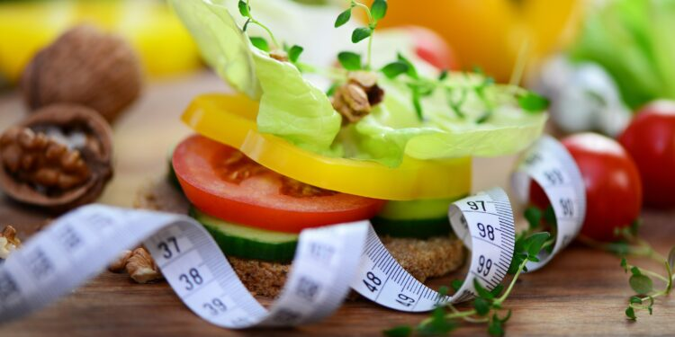Ein mit Gemüse belegtes Vollkornbrot neben einem Maßband
