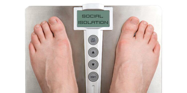 """Füße auf der Wage mit """"Social Isolation""""."""