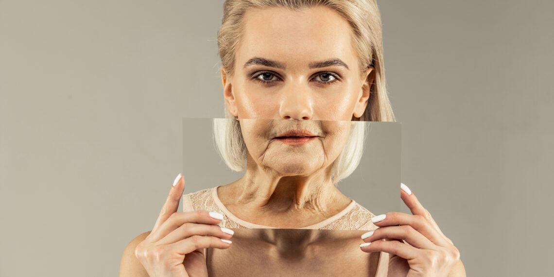 Eine junge Frau hält ein Bild einer älteren Frau über Teile ihres Gesichts.