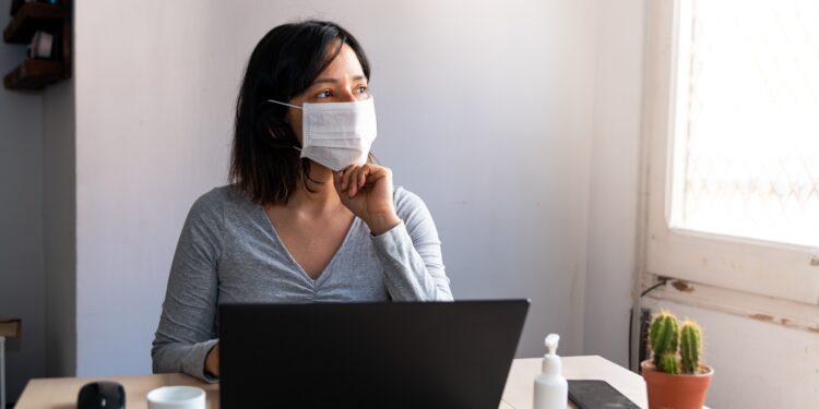 Frau mit Mund-Nasen-Bedeckung sitzt vor ihrem Laptop und sieht aus dem Fenster