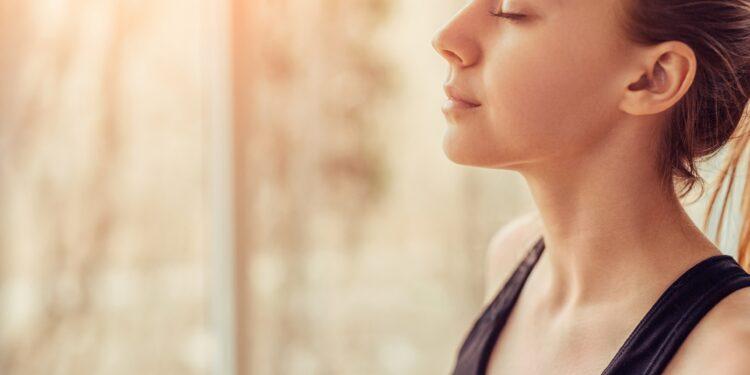 Junge Frau führt eine Atemübung aus.